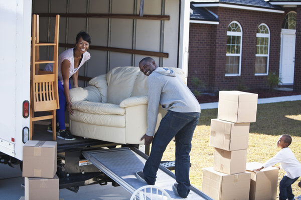 African American family moving house.  Couple (30s) loading or unloading moving van.